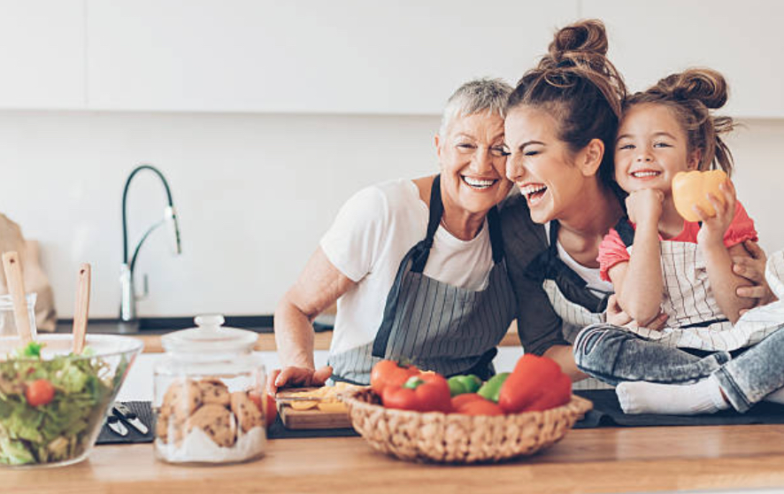 three generations of women in the kitchen hugging