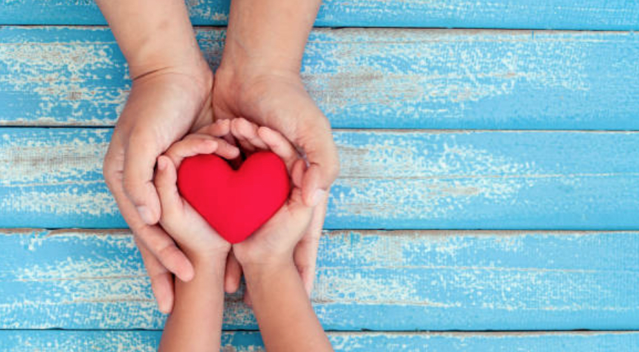 a young pair of hands coupling a heart and an adult pair of hards coupling the young hands