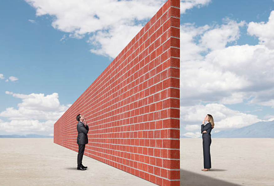 two people separated by a brick wall