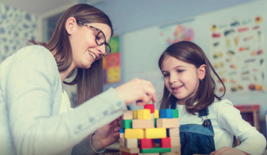 A teacher interacting with a young child building blocks.