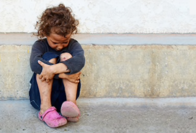 Young homeless girl sitting in the street.