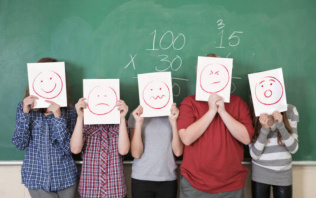 young children holding up different faces with emotions