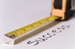 The word success being measured by a tape measure.