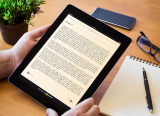 Image shows a tablet displaying a book page on a desk surrounded by writing utensils, glasses, and a plant.
