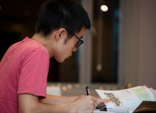 Image shows student studying from a textbook at a table