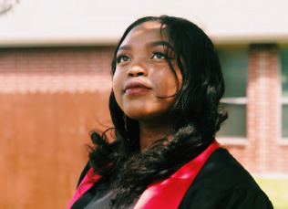 Young woman in graduation gown looking upward