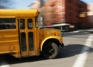 Image of school bus with blurred city background